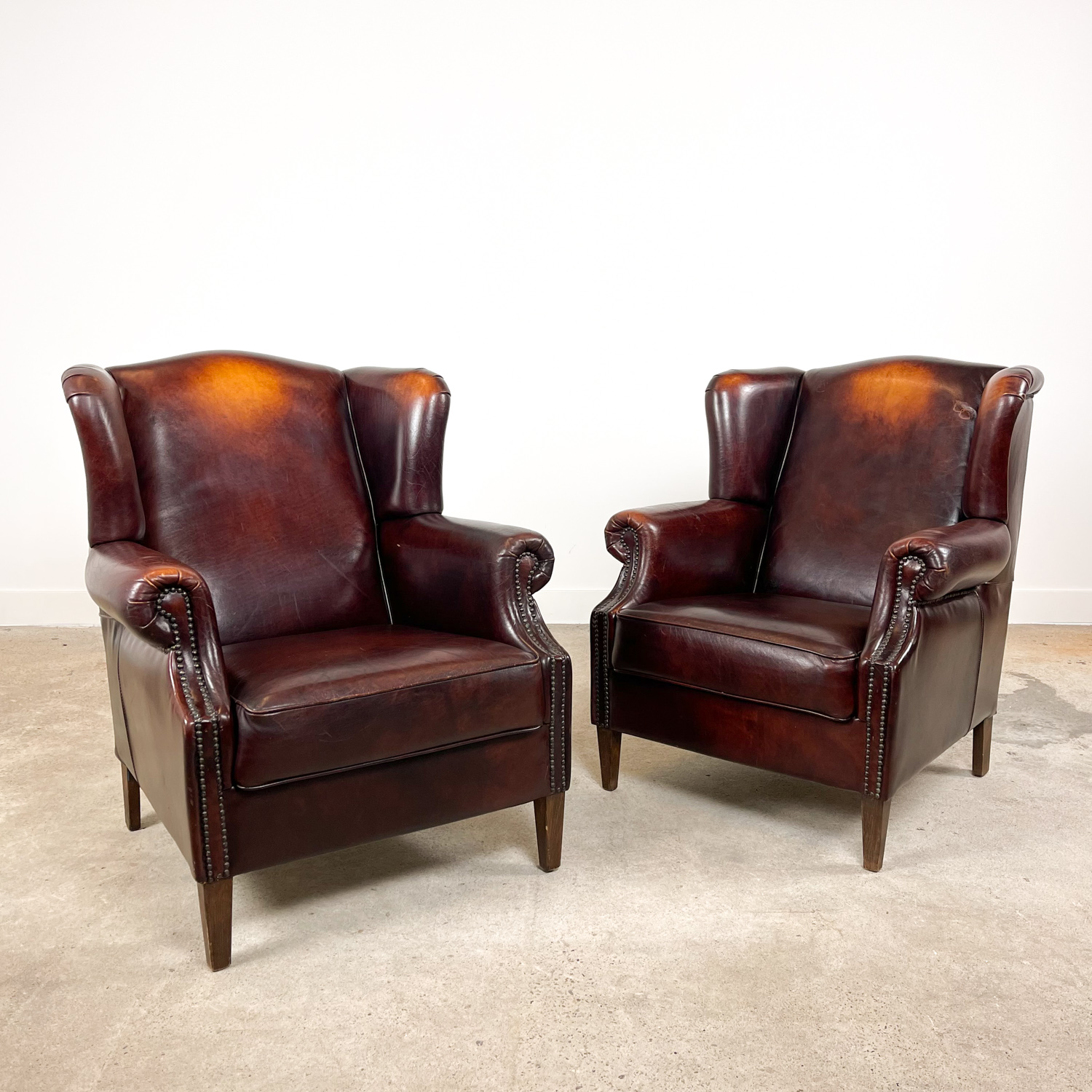 Set of two vintage dark brown sheep leather wingback armchairs