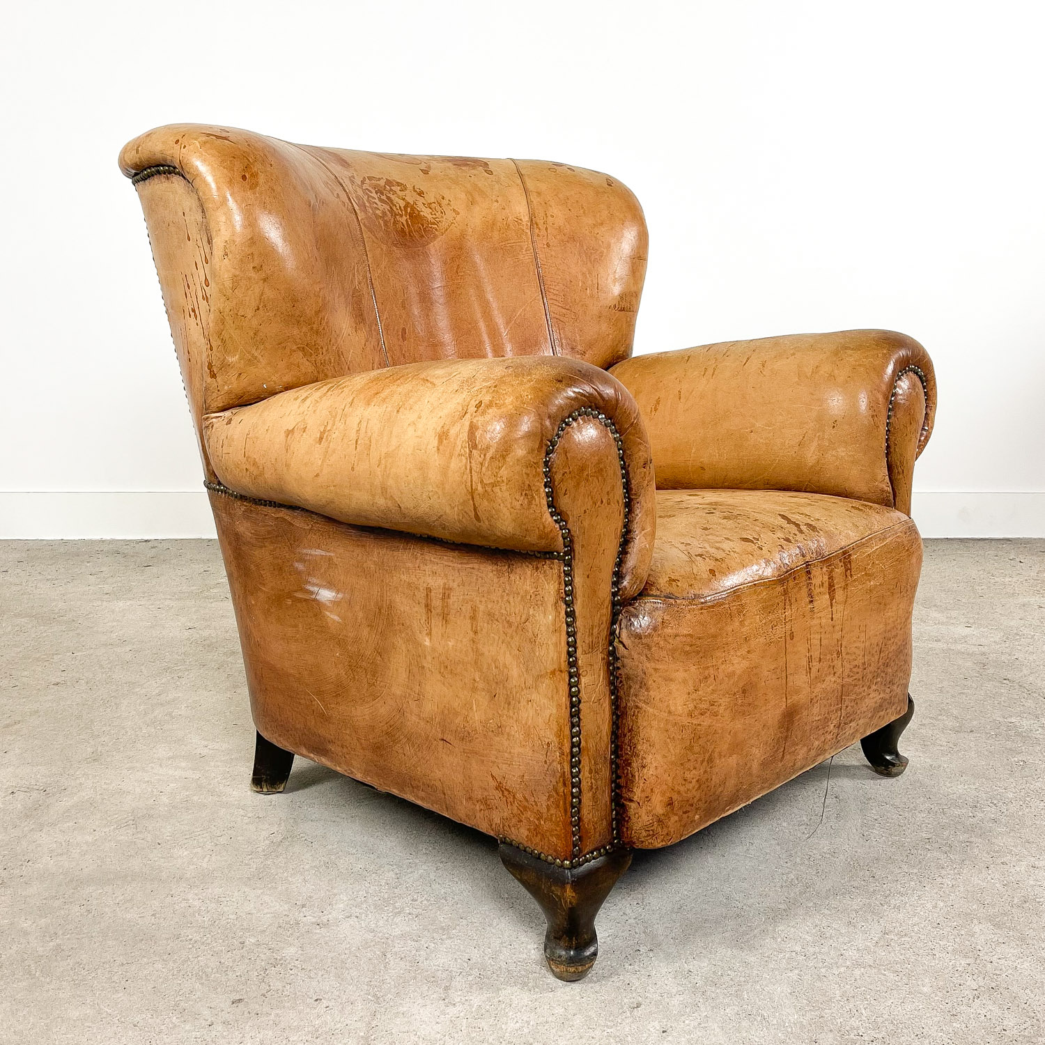 Antique cognac colored sheep leather armchair Big bertha